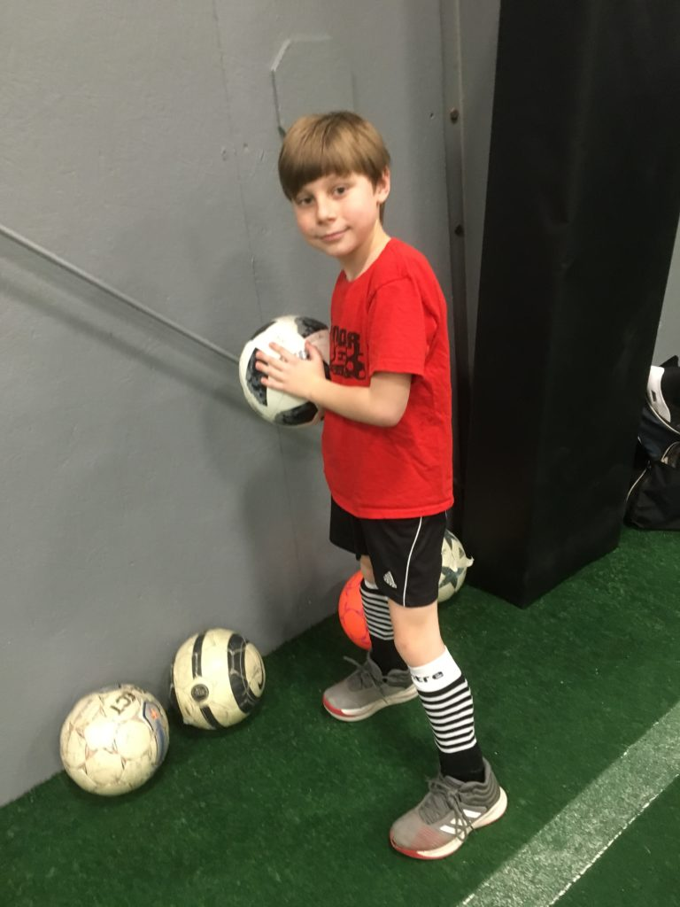 Jonathan holding a soccer ball in his soccer uniform, smiling.